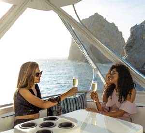 Two women enjoying a drink while boating in Los Cabos
